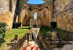 A glass of white Crémant de Bordeaux with the roofless ruined church of Les Cordeliers in the background