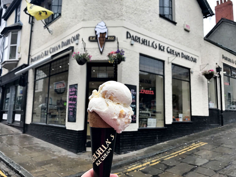 Jennifer holds a cone with two scoops of ice cream in front of Parisella's in Conwy