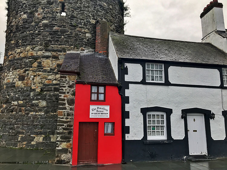 The smallest house in Great Britain is painted red and is next to a white and black house in Conwy, Wales