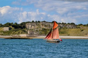 A red sailboat sails past ruins on the Anglesey coast near Beaumaris