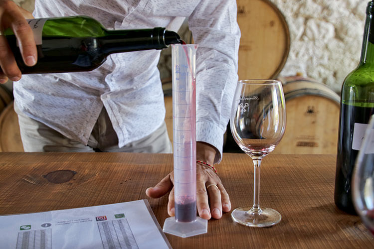 Pouring the wine into a graduated cylinder in the B. Winemaker Workshop