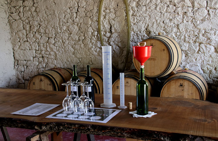 Five glasses sit on a placement with bottles of the Merlot and Cabernet and graduated cylinders for the B. Winermaker Workshop at Château Fombrauge