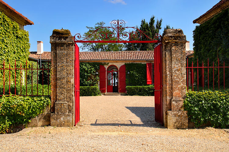 A red gate frames the single level former stone farmhouse with red doors and shutters
