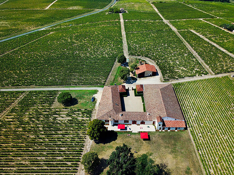 A drone aerial of Château Sigalas Rabaud surrounded by their vineyards