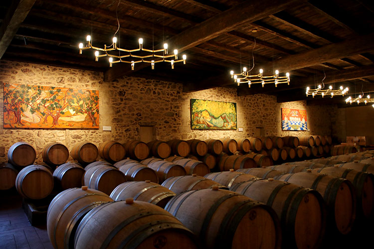 The barrel room is the old stable with wooden beams and artworks lining the stone walls