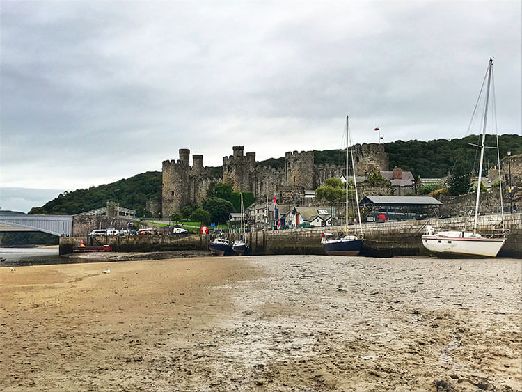 Conwy Castle seen from the beach while tide is out in Conwy
