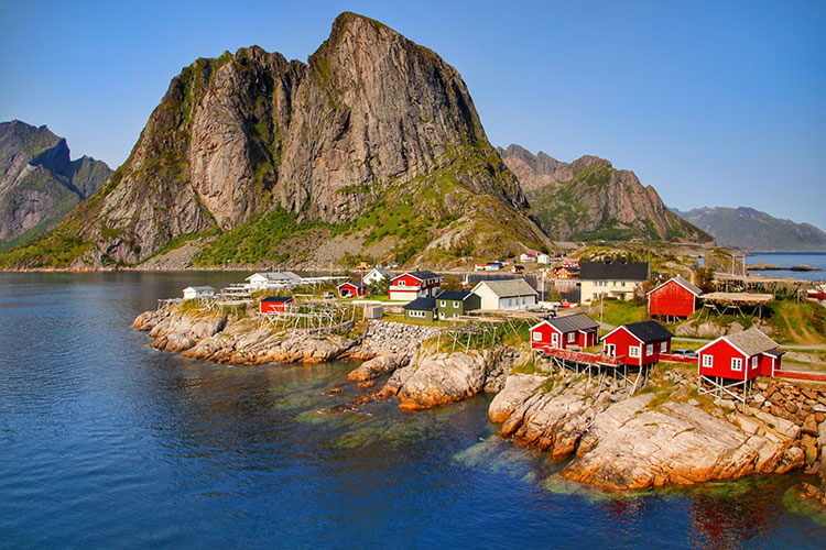 Red and green wooden houses of the village of Hamnøy sit on rocks under a vertical mountain in the Lofoten Islands