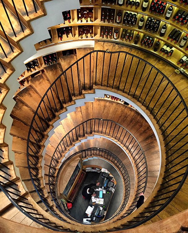 Looking down the spiral wooden staircase at L'Intendant Grands Vins de Bordeaux which is lined with over 1200 wines from the Bordeaux wine region