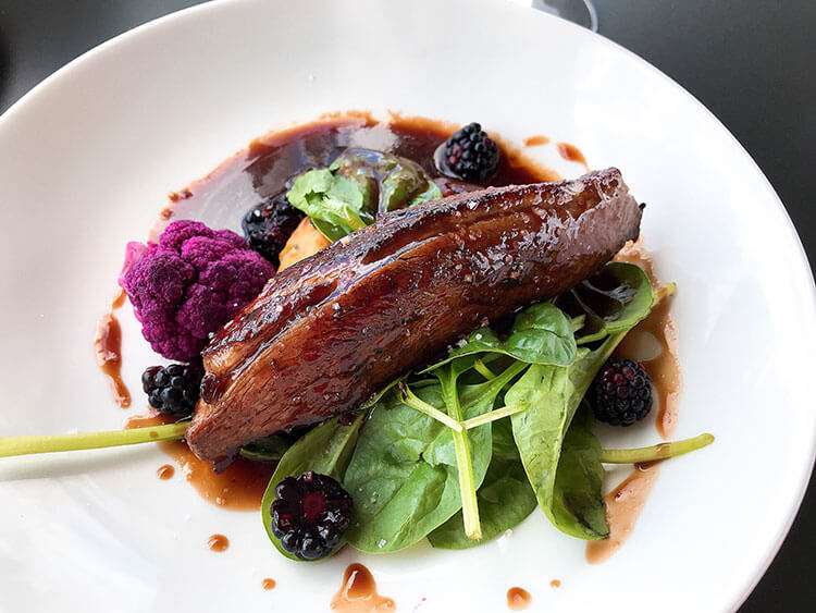 Duck breat on a bed of greens with purple cauliflower and balckberries at La Terrasse Rouge