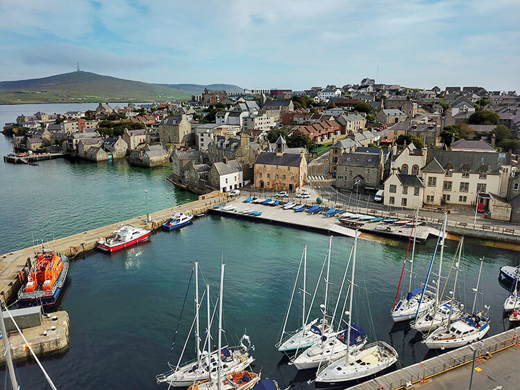 A drone shot of Lerwick's stone buildings rising up beyond Lerwick Harbor
