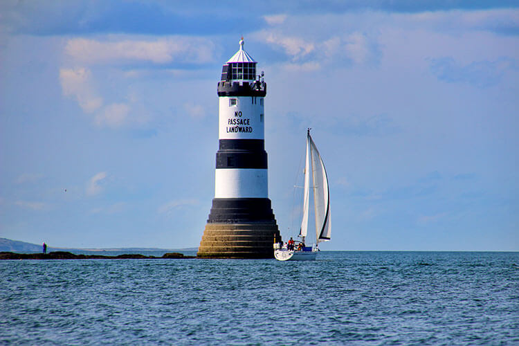 A sailboat sails past the black and white striped Penmon Lighthouse in Wales