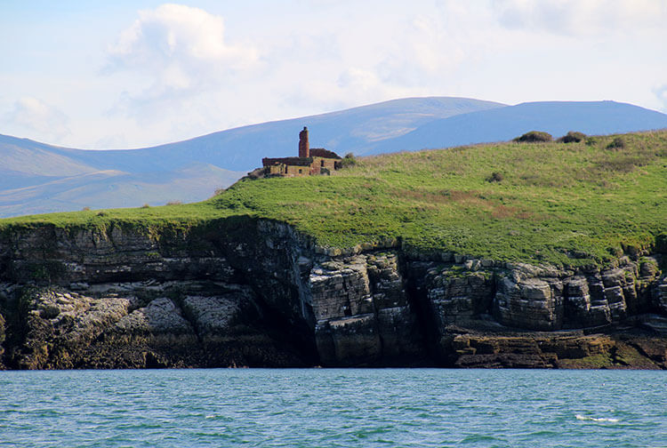 The ruined monastery Ynys Seiriol stands on a grassy hilltop on Puffin Island as seen from the sea passing by