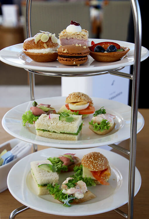 A three-tiered tea tower with the top with four desserts, and two tiers of finger sandwiches in the Wintergarden on Viking Sea