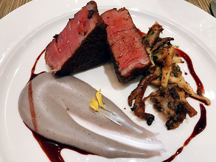 A beef tenderloin filet cut in half and served with purple mashed potatoes and mushrooms