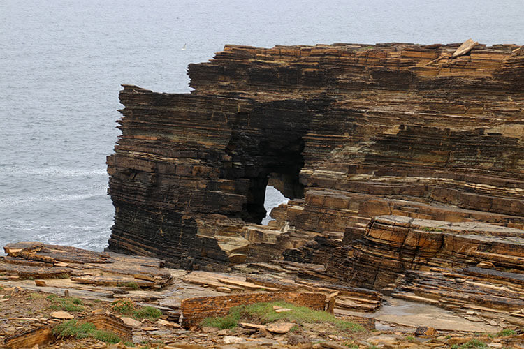 "The layered red sandstone of the Yesnaby Cliffs with a ""window"" cut out by the sea"