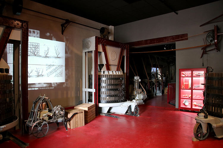 The first room of Vitishow with three presses and various tools and equipment used in the vineyard in 1920