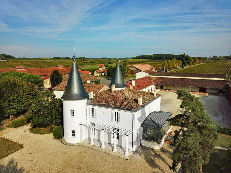 A drone aerial of Château de Seguin's main house with its gray topped towers
