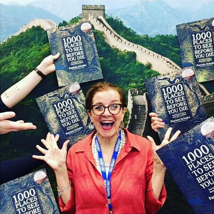 Patricia Shultz, author of 1000 Places to See Before You Die, stands on the Great Wall of China with her new hard cover coffee table book