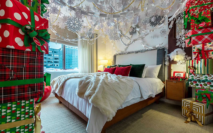 The bedroom of the Elf Suite at Club Wyndham Midtown 45 with paper snowflakes hanging from the ceiling, red and green Christmas pillows and a gift box mural wall