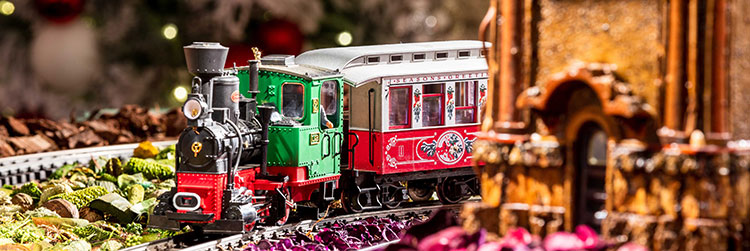 A holiday themed model train in red, white and green on the track at the Holiday Train Show at the New York Botanical Garden