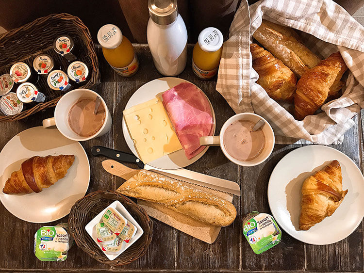 Breakfast with baguettes, croissants, meat, cheese, juice and hot chocolate