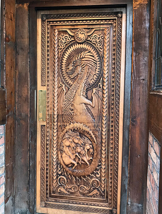 The door at Fullerton Arms is carved with a fearsome dragon clutching horses in its talons