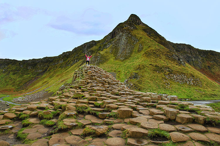 Jennifer on a raised section of Giant's Causeway with the green mountains rising up behind