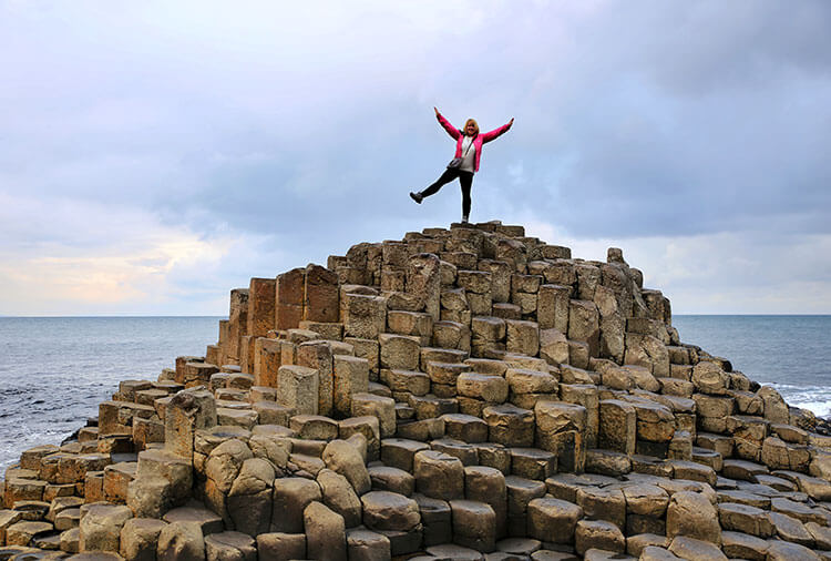Jennifer poses on one leg atop the section known as the Honeycomb at Giant's Causeway