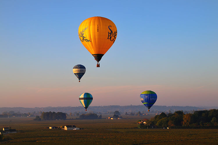 Four hot air balloons at sunrise rising over the vineyards of Saint-Emilion in the Bordeaux wine region