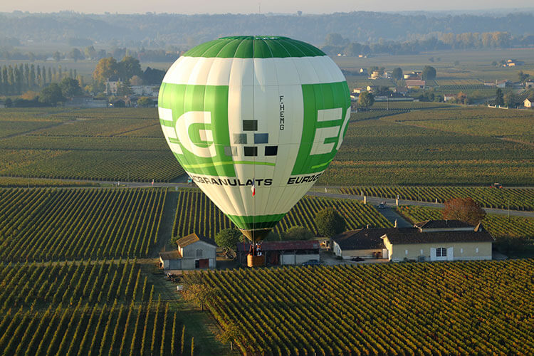 The green and white Girone hot air balloon flying low over a château and vineyards in Saint-Émilion