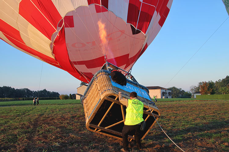 The pilot gets the hot air balloon ready on the ground by using bursts from the burners in Saint-Émilion