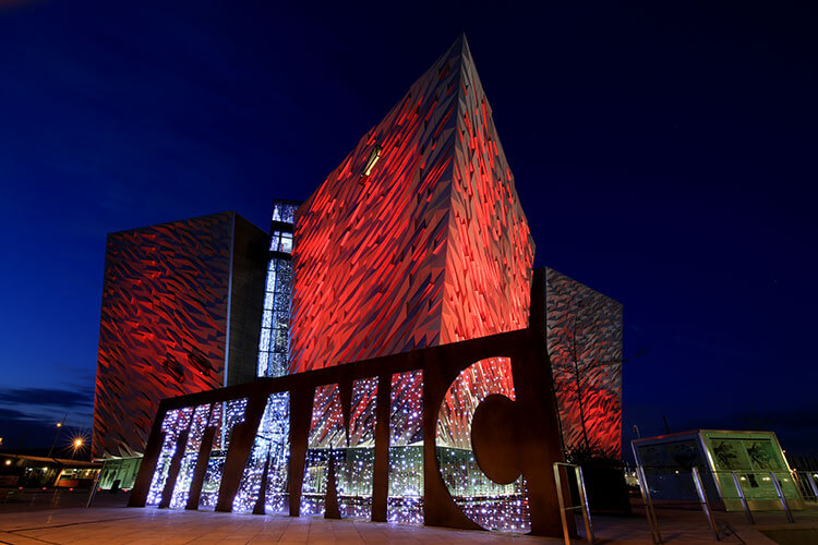 The Titanic Belfast building lit up in red in Belfast