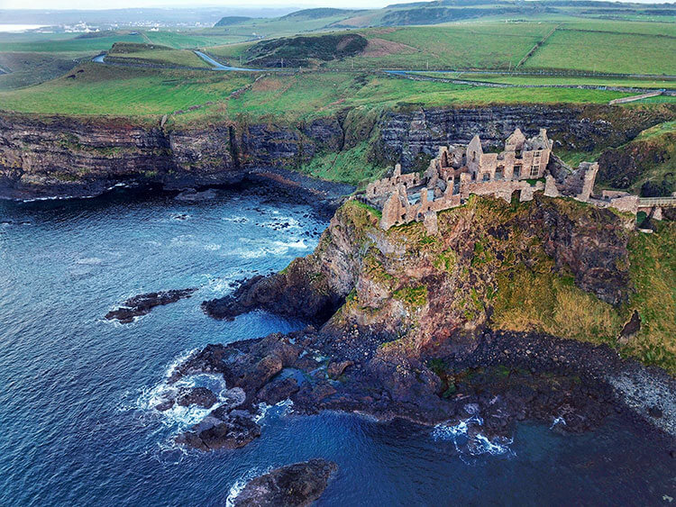 Drone aerial of the coastal cliffs with Dunluce Castle perched on the cliffside