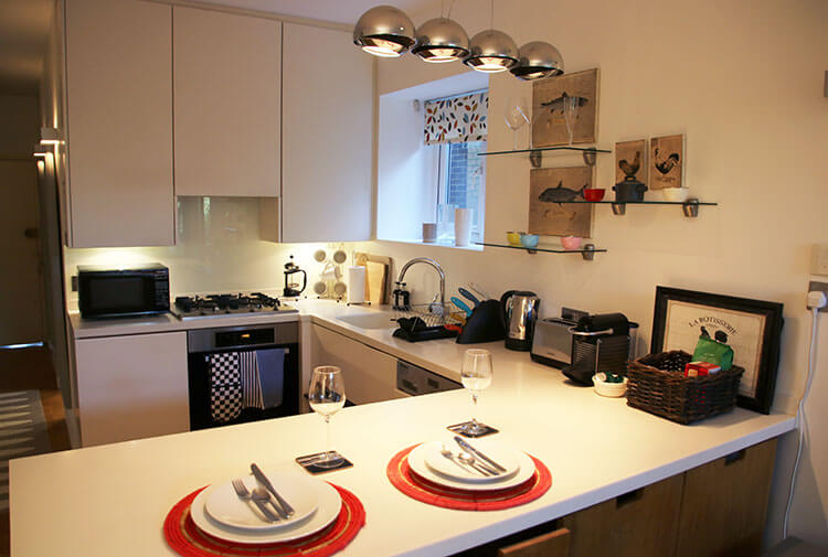 Fully equipped kitchen with stove top, oven, microwave, dishwasher, Nepresso machine and tea kettle in London Perfect's Hamilton apartment