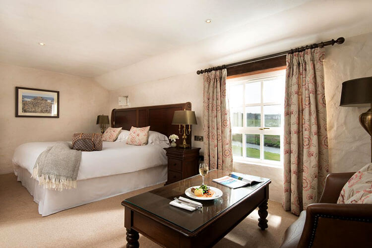 Our room with large king bed and river view decorated in beiges and browns at The Bushmills Inn