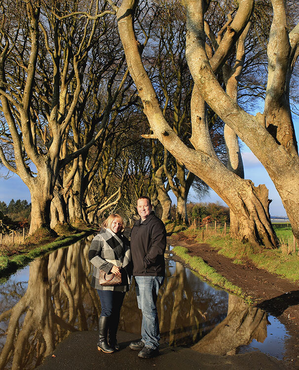 Jennifer and Tim at The Dark Hedges after a rainstorm, with the trees reflected in a puddle on the road