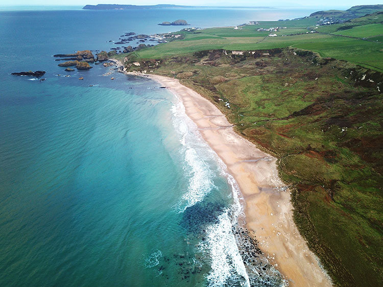 Drone shot showing stretch of white sand beach and the rising green cliffs of White Park Bay