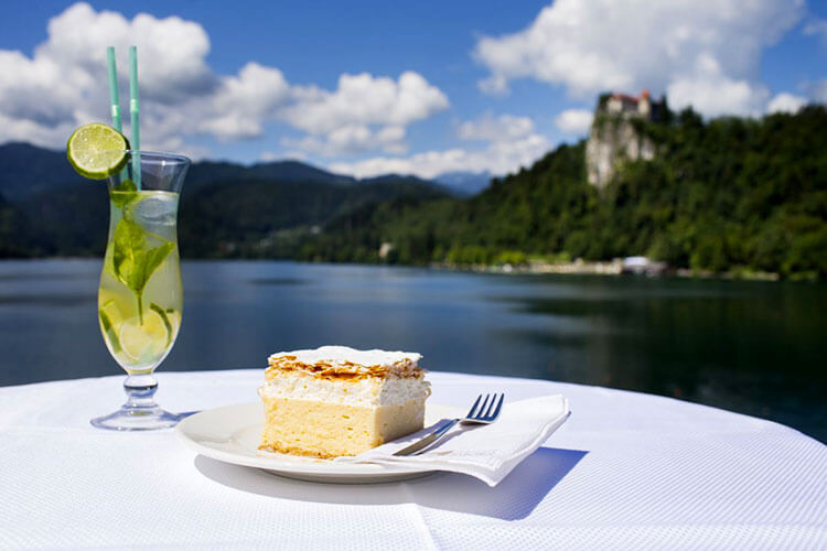 A piece of the original Bled cake with a view of Bled Castle at The Panorama Restaurant in Lake Bled