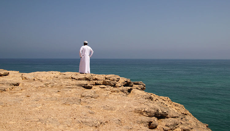 Our Anantara guide stands looking out to sea from the edge of a cliff in Salalah