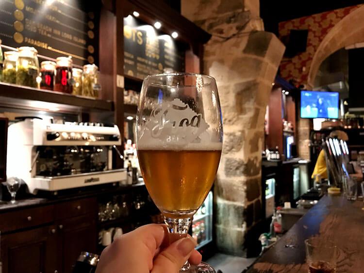 Jennifer holding up a Frog beer in the bar area at the Frog & Rosbif Bordeaux