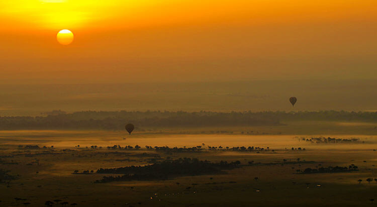 Two hot air balloons float above the Mara River as the sky turns shades of orange and the sun appears as a fiery ball at sunrise