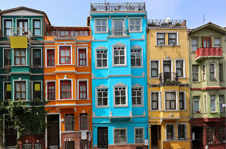 A row of five colorful houses in green, orange, blue, yellow, and mint green in the Balat neighborhood in Istanbul