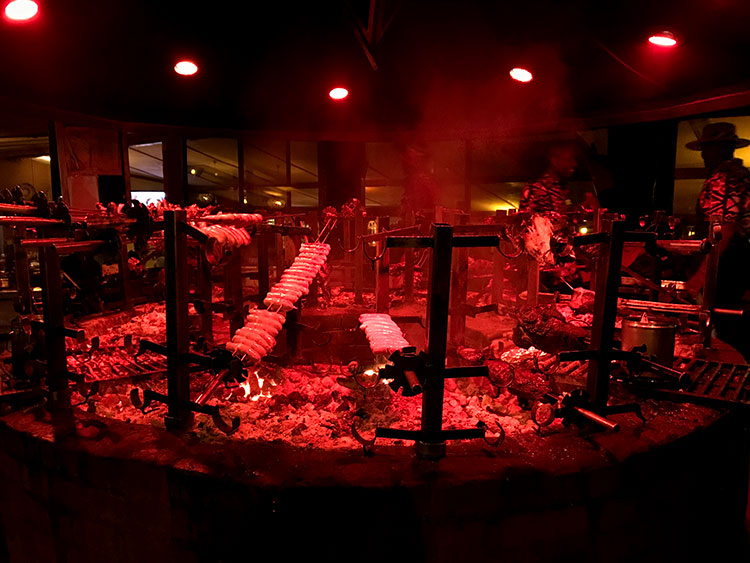 The massive barbecue pit at Carnivore with various meat and sausages cooking and smoke rising