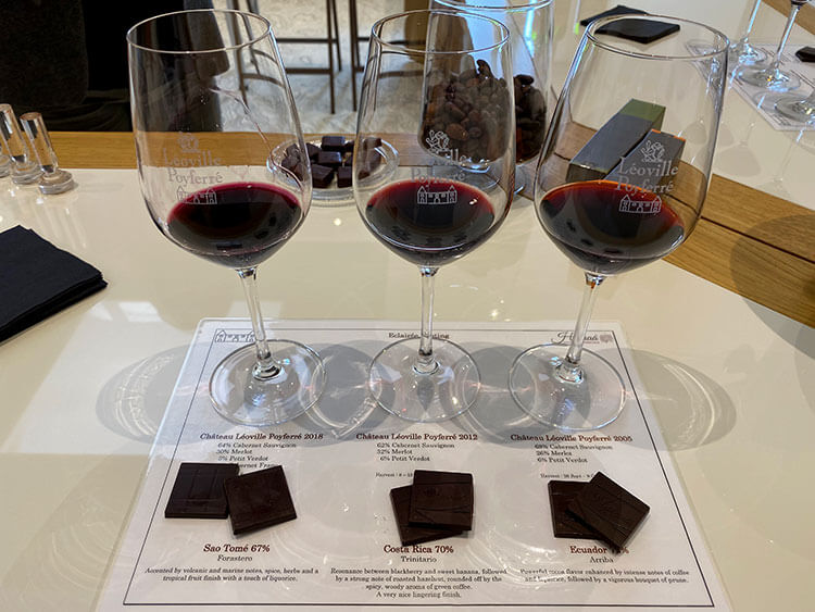 Three glasses of the 3 vintages with 2 pieces of three different origin chocolates on a placement with the wine and chocolate tasting notes at Château Léoville-Poyferré