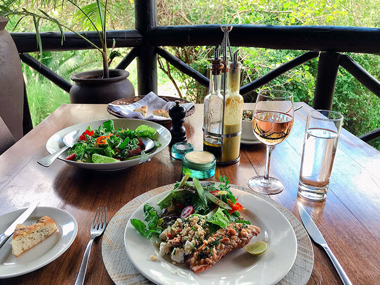 Lunch at The Emakoko with cashew crusted red snapper, garden salad with edible flowers and a glass of rosé wine