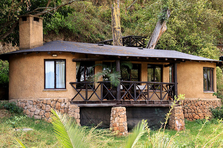 The exterior of the cottages at The Emakoko with a light brown stucco to blend in to the hillside and dark wood balcony