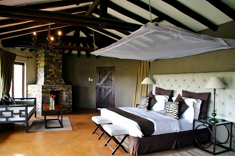 The bedroom of The Emakoko's cottage with queen size bed in brown, white and zebra print linens and a stone fireplace in the corner with a small couch for seating area in front of the fireplace