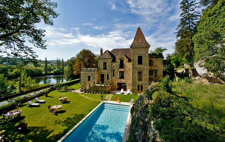 The outdoor pool with Château de la Malartrie sitting on the edge of the Dordogne River