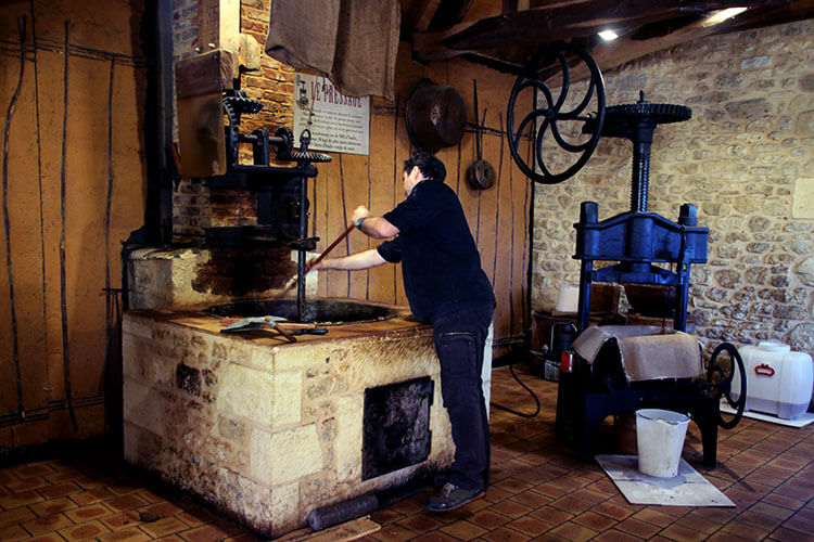 A worker stirs the dough as it heats in a large cast iron pot at the Ecomusée de la Noix