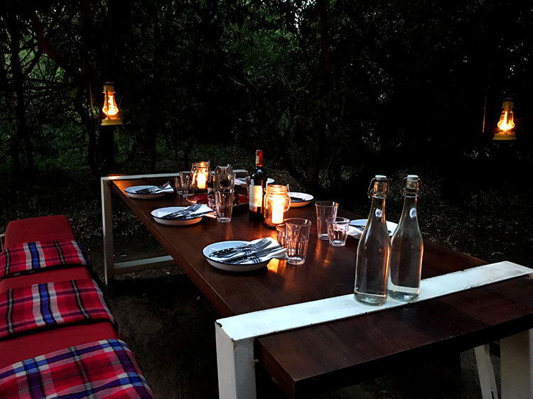 A picnic table set for the bush barbecue and lit by hanging lanterns